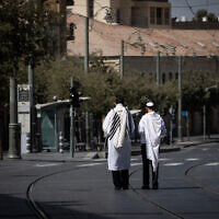 Men walk with prayer shawls in Jerusalem on Yom Kippur, the Day of Atonement, September 28, 2020 (Yonatan Sindel/Flash90)