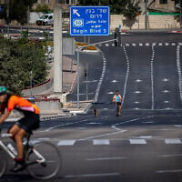 People ride their bicycles along the empty street in Jerusalem, on Yom Kippur, September 28, 2020 (Yonatan Sindel/Flash90)