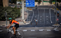 People ride their bicycles along the empty road in Jerusalem, on Yom Kippur, September 28, 2020 (Yonatan Sindel/Flash90)