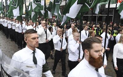 ILLUSTRATIVE -- Members of the far-right Nordic Resistance Movement march through the town of Ludvika, central Sweden, on May 1, 2018. (Ulf Palm/AFP via Getty Images via JTA)