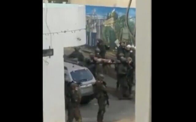 A screenshot from a video published September 5, 2020, showing Israeli troops carrying a pair of Palestinians on stretchers in the West Bank city of Jenin. (Screen capture: Twitter)