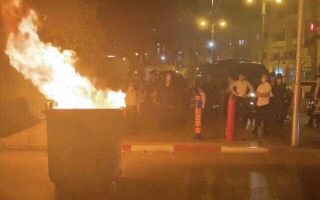 Ultra-Orthodox protesters burn a trash dumpster in Bnei Brak on September 20, 2020. (Screen capture: Twitter)