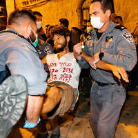 Police remove demonstrators who were blocking a road during a protest against Prime Minister Benjamin Netanyahu outside his official residence in Jerusalem, September 20, 2020. (Olivier Fitoussi/Flash90)