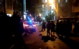 Bnei Brak residents surround a police vehicle enforcing a nightly curfew, September 13, 2020. (Screen capture: Twitter)