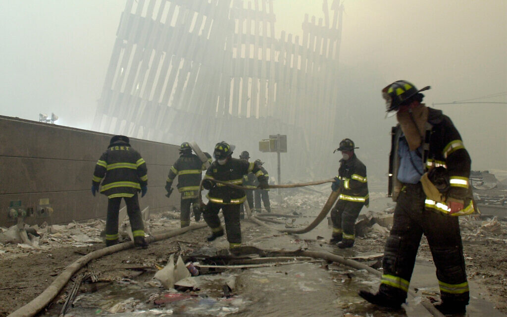 Firefighters work beneath the destroyed mullions, the vertical struts that once faced the outer walls of the World Trade Center towers, after the terrorist attack on the twin towers in New York, September 11, 2001. (AP Photo/Mark Lennihan, File)