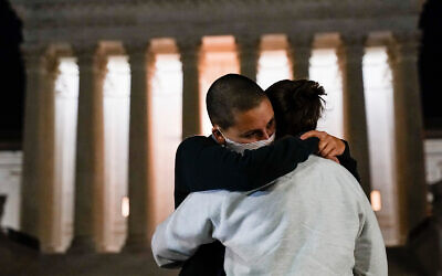 A couple hugs outside the Supreme Court following Justice Ruth Bader Ginsburg's death, in Washington, September 18, 2020. (AP Photo/Alex Brandon)