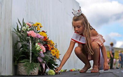 A girl places a flower at the Wall of Names at the Flight 93 National Memorial in Shanksville, Pennsylvania, Sept. 10, 2020. (AP Photo/Gene J. Puskar)