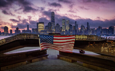 A US flag hanging from a steel girder, damaged in the Sept. 11, 2001 attacks on the World Trade Center, blows in the breeze at a memorial in Jersey City, N.J., Sept. 11, 2019. (AP Photo/J. David Ake)