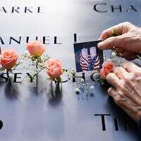 Mourners place flowers and pictures at the National September 11 Memorial and Museum in New York, September 11, 2020. (AP Photo/John Minchillo)
