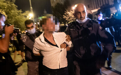 Police officers arrest a man who allegedly sped in his car toward protesters during a protest against Prime Minister Benjamin Netanyahu outside his official residence in Jerusalem, September 20, 2020. (Yonatan Sindel/Flash90)