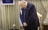 President Reuven Rivlin lights a memorial candle for coronavirus victims during a video message ahead of Yom Kippur, September 27, 2020. (Screen capture: YouTube)