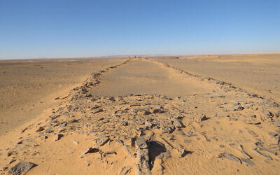 A massive, ancient stone structure in Saudi Arabia, with platforms at both ends and connecting walls in between. Two barely visible researchers standing at the far end provide a sense of scale. (courtesy/ Huw Groucutt/ The Holocene)