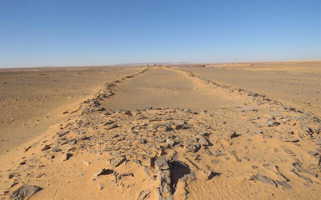 A massive, ancient stone structure in Saudi Arabia, with platforms at both ends and connecting walls in between. Two barely visible researchers standing at the far end provide a sense of scale. (courtesy/ HuwGroucutt/ The Holocene)