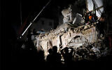 Lebanese and Chilean rescuers search a collapsed building in Beirut, Sept. 4, 2020. (AP Photo/Hussein Malla)