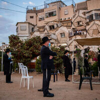 Men hold prayers outdoors in Jerusalem on September 9, 2020. (Yonatan Sindel/Flash90)