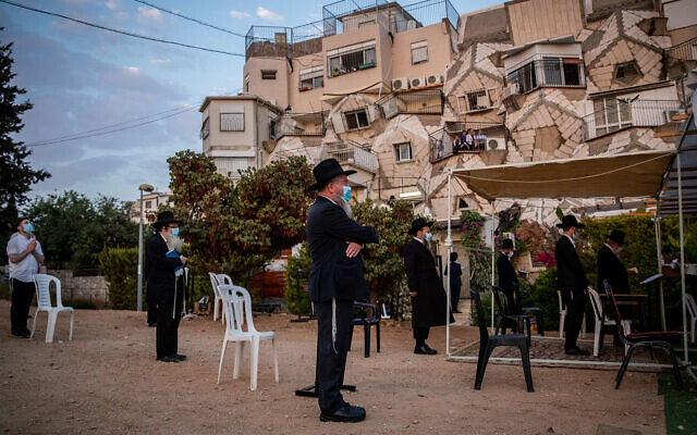 Men hold prayers outdoors in Jerusalem on September 9, 2020. (Yonatan Sindel/Flash90)