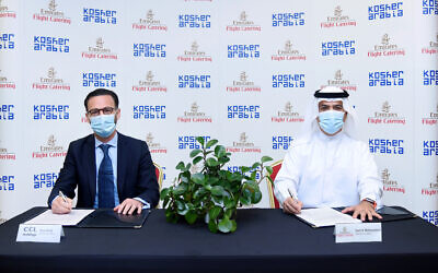 Ross Kriel, left, and Emirates Flight Catering CEO Saeed Mohammed signing an MOU about cooperating on kosher meals produced locally, Abu Dhabi, September 17, 2020 (courtesy Emirates)