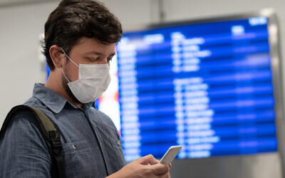 A mask-wearing traveler looks at his cellphone in front of a flight panel (Vergani_Fotografia; iStock by Getty Images)