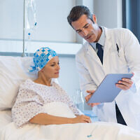 Doctor showing medical records to cancer patient in hospital ward (Ridofranz; iStock by Getty Images)