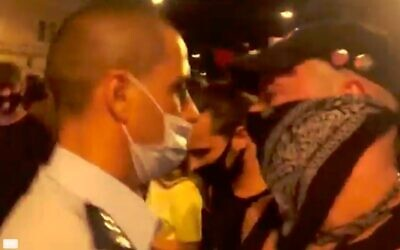 Jerusalem police officer Koby Yaakobi wears a mask with his nose exposed while standing among a crowd of protesters demonstrating against Prime Minister Benjamin Netanyahu outside his official residence in Jerusalem on Sunday, September 20, 2020. (Screen capture/Ynet News)