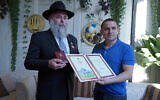 Rabbi Yonatan Markovitch, left, holds up a medal and a certificate he received at the parliament of Ukraine in Kyiv, September 7, 2020. (Courtesy of Markovitch via JTA)