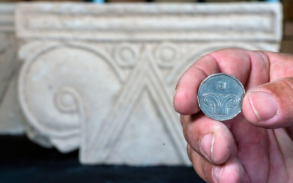 A five-shekel coin juxtaposed with a column head found at Armon HaNatziv (Yaniv Berman, Israel Antiquities Authority)