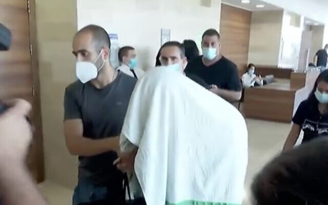 Screen capture from video of one of the suspects in a gang rape in Eilat arriving at the Beersheba District Court, September 3, 2020. (Channel 13 news)