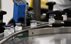 Vials of a potential coronavirus vaccine are seen on an assembly line in a photograph released by Israel's Institute for Biological Research on October 25, 2020. (Defense Ministry)