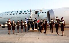 The crew of an Etihad Airlines flight wave Israeli flags after landing at Ben Gurion Airport, October 19, 2020 (Sivan Farag)