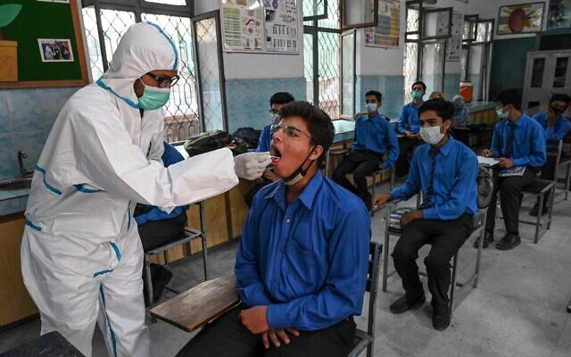 A health official (L) collects a swab sample from a student to test for the Covid-19 coronavirus at a government school in Lahore on October 1, 2020, after the educational institutes reopened nearly six months after the spread of the Covid-19 coronavirus. (Arif ALI / AFP)