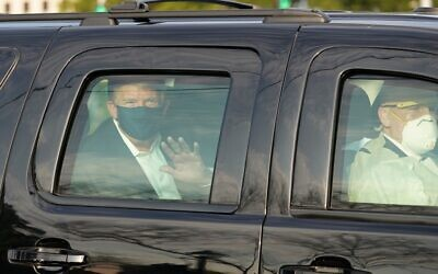 US President Donald Trump waves from the back of a car in a motorcade outside of Walter Reed Medical Center in Bethesda, Maryland on October 4, 2020. (Photo by ALEX EDELMAN / AFP)