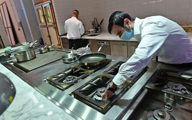 Rabbi Yaakov Eisenstein (R) supervises the preparation of food Elli's Kosher Kitchen, in Dubai, on October 5, 2020 (GIUSEPPE CACACE / AFP)
