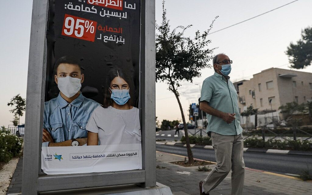 A man walks past an advert sign posted by Israel's health ministry instructing people in Arabic to wear face masks as a prevention method of COVID-19 coronavirus disease in the Arab neighbourhood of Sheikh Jarrah in east Jerusalem on October 8, 2020. (Photo by Ahmad GHARABLI / AFP)