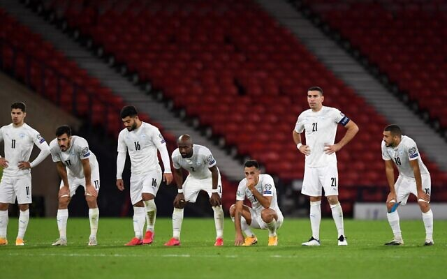 Israeli players watch the penalty shootout during the Euro 2020 playoff semi-final soccer match between Scotland and Israel at Hampden Park, Glasgow, on October 8, 2020. (Andy Buchanan/AFP)