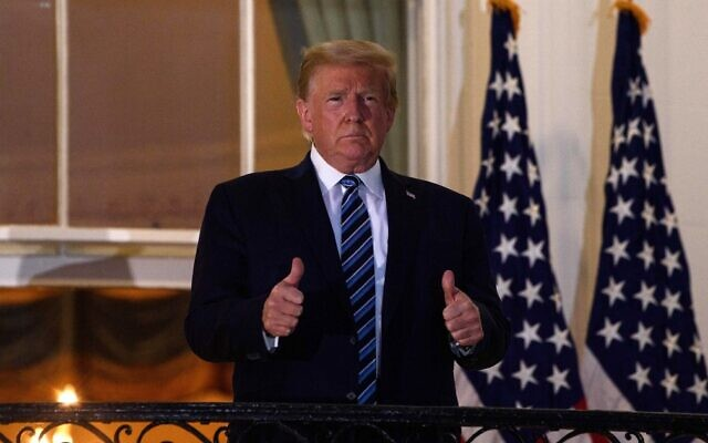 US President Donald Trump gives two thumbs up from the Truman Balcony upon his return to the White House in Washington from Walter Reed Medical Center, where he underwent treatment for COVID-19, October 5, 2020. (Nicholas Kamm/AFP)