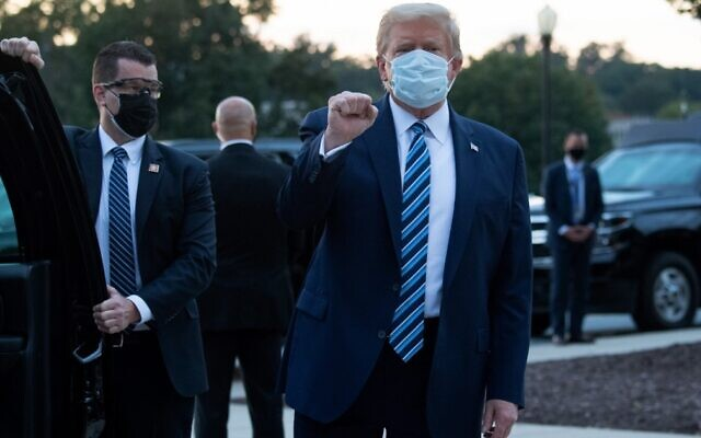 US President Donald Trump pumps his fist as he leaves Walter Reed Medical Center in Bethesda, Maryland, to return to the White House after being discharged, October 5, 2020. (Saul Loeb/AFP)