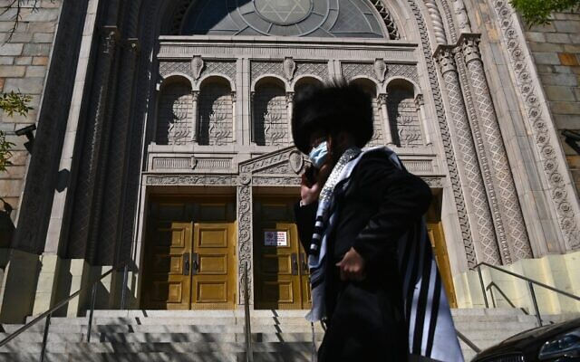 A Hasidic Jew walks past a closed synagogue  in the Borough Park section of Brooklyn, one of the five boroughs of New York City, on October 9, 2020.  (Angela Weiss / AFP)