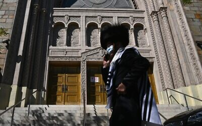 A Hasidic Jew walks past a closed synagogue  in the Borough Park section of Brooklyn, one of the five boroughs of New York City, on October 9, 2020. (Angela Weiss/AFP)
