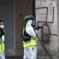 A municipal worker cleans swastikas spray painted on columns of the Rivoli Street in central Paris on October 11, 2020. (STEPHANE DE SAKUTIN/AFP)