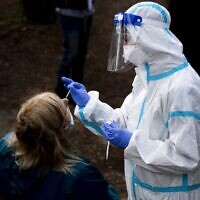 A woman undergoes a swab test for coronavirus at a drive-through testing site of the Santa Maria della Pieta hospital in Rome on October 12, 2020. (Tiziana Fabi/AFP)