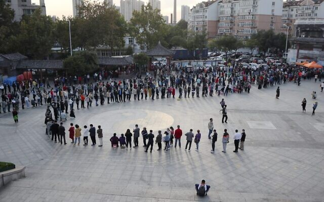 This photo taken on October 12, 2020 shows residents lining up to be tested for the COVID-19 coronavirus, as part of a mass testing program following a new coronavirus outbreak in Qingdao, in China's eastern Shandong province. (STR / AFP) / China OUT