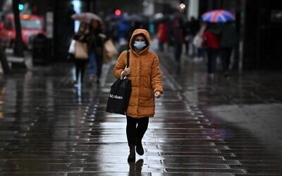 A pedestrian wearing a face mask or covering due to the COVID-19 pandemic, walks in the rain on Oxford Street in London on October 13, 2020, (DANIEL LEAL-OLIVAS / AFP)