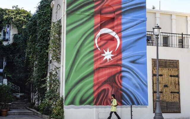A woman walks past a building with a painting of the Azerbaijani flag on its wall in Baku on October 14, 2020, amid the ongoing military conflict between Armenia and Azerbaijan over the breakaway Nagorno-Karabakh region. (TOFIK BABAYEV / AFP)