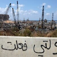 """Arabic graffiti drawn on the side of a road reading """"my government did this"""" is seen in front of the cranes at the port of Lebanon's capital Beirut, while in the background are the damaged grain silos opposite the blast site of a colossal explosion, August 9, 2020. (Patrick Baz/AFP)"""