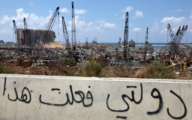 "Arabic graffiti drawn on the side of a road reading ""my government did this"" is seen in front of the cranes at the port of Lebanon's capital Beirut, while in the background are the damaged grain silos opposite the blast site of a colossal explosion, August 9, 2020. (Patrick Baz/AFP)"