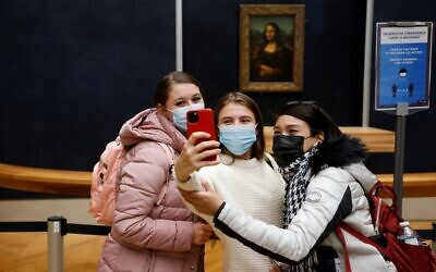 Visitors wearing protective face masks take pictures in front of Leonardo Da Vinci painting 'Mona Lisa' (La Gioconda) inside the deserted Louvre Museum in Paris on October 14, 2020. (Ludovic MARIN / AFP)