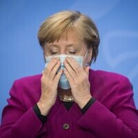 German Chancellor Angela Merkel puts on her a mask at the end of a press conference following a meeting of states' leaders on the coronavirus situation in Berlin on October 14, 2020. (STEFANIE LOOS / various sources / AFP)