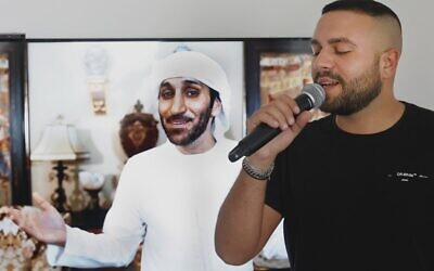 Israeli singer Elkana Marziano, 28, sings along with a video clip of a song on which he worked in collaboration with Emirati artist Walid Aljasim (image on screen), during an interview with AFP at his home in the central Israeli city of Giv'at Shmuel, on October 15, 2020. (Photo by JACK GUEZ / AFP)