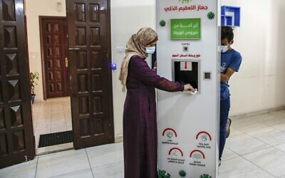 Palestinian entrepreneur Heba al-Hindi demonstrates a locally designed and manufactured smart sterilization device in Gaza City on October 8, 2020, as the machine is to be to be deployed across various facilities in the Gaza Strip as part of efforts to curb the spread of COVID-19 coronavirus disease (MOHAMMED ABED / AFP)