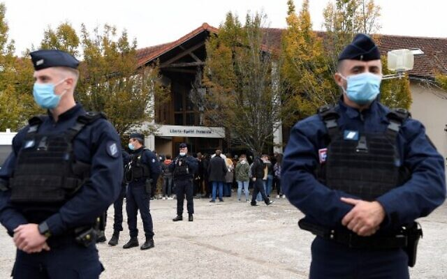 French police officers stand as adults and children gather in front of flowers displayed at the entrance of a middle school in Conflans-Sainte-Honorine, on October 17, 2020. (Bertrand GUAY / AFP)